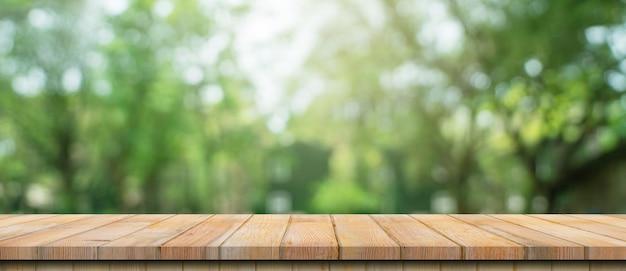 空の木製テーブルと焦点がぼけたボケ味と日光で庭の木の背景をぼかします。製品展示
