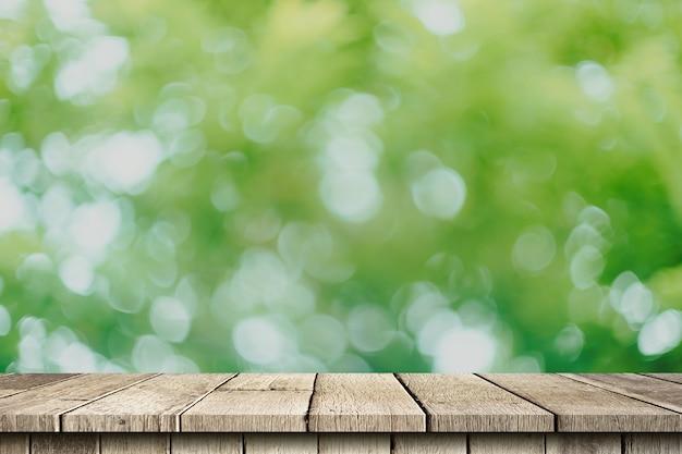 空の木製テーブルと緑のボケ味が、製品のコピースペース表示モンタージュでぼやけています。