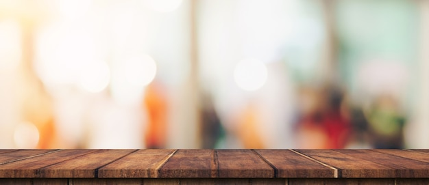 Empty wood table and blurred light table in shopping mall with bokeh background. product display template.