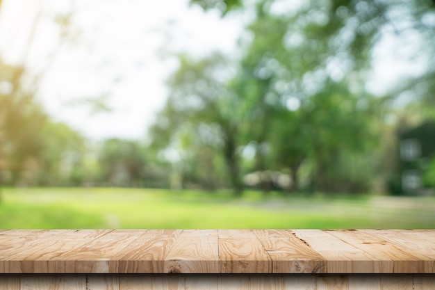 Empty wood table and defocused bokeh and blur background of garden trees with sunlight. product display template.