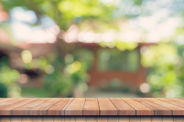 Empty wood table and defocused bokeh and blur background of garden trees with sunlight. product display.