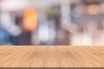 Empty wood table in front with blurred background of coffee shop