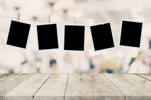 Empty wood table and instant photo hanging on blur image background of people display mont