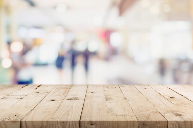 Empty wood table and people in shopping in department store