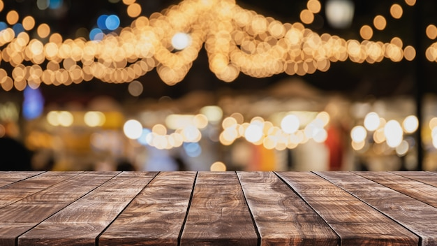 Empty wood table top on abstract blurred restaurant and nightclub party lights background