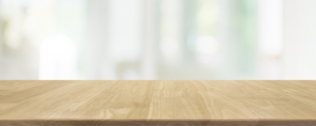 空の木製のテーブルトップとぼやけたガラス窓のインテリアレストランのバナーは抽象的な背景をモックアップします-あなたの製品を表示したりモンタージュしたりするために使用できます。