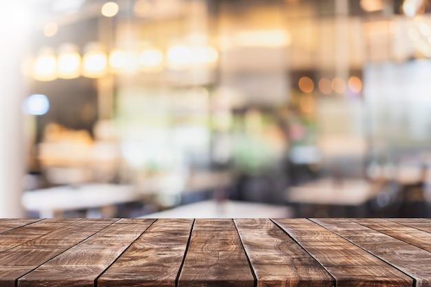 Пустая деревянная столешница и размытый интерьер кафе и ресторана
