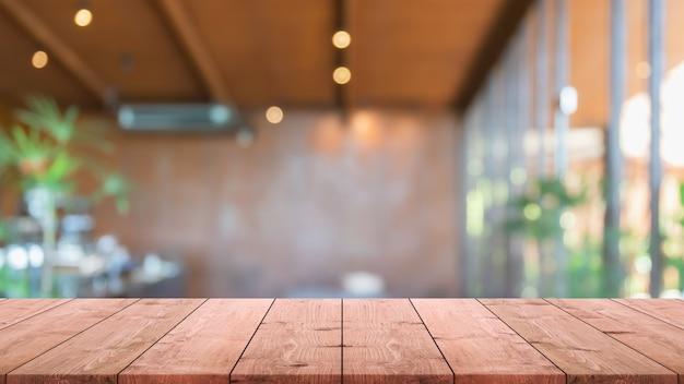 空の木のテーブルトップとぼやけたコーヒーショップ