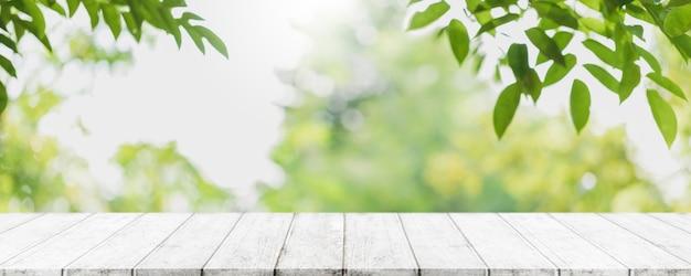 Пустая деревянная столешница и размытое зеленое дерево в парковом саду