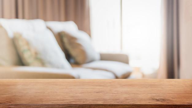 空の木製のテーブルトップとカーテンの窓の背景を持つ家のインテリアのぼやけたリビングルーム。 -製品の展示やモンタージュに使用できます。