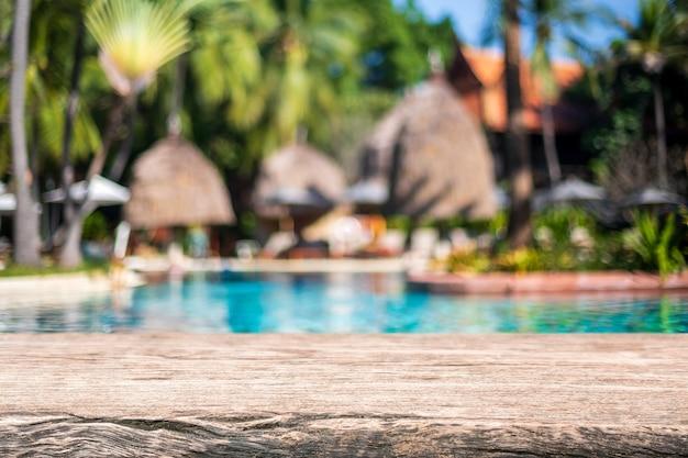 Пустая деревянная столешница и размытый бассейн на тропическом курорте летом