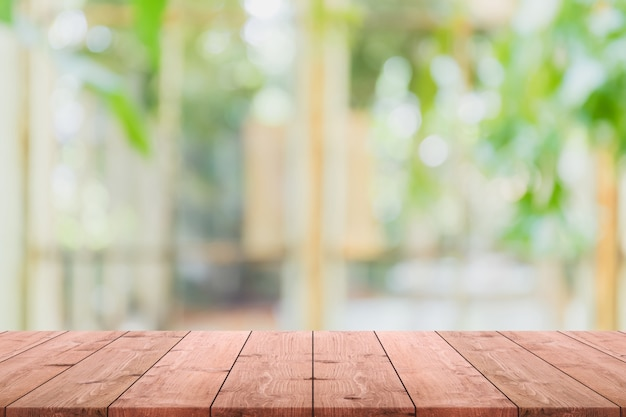 Empty wood table top and blurred of interior room with window view from green tree garden background background.