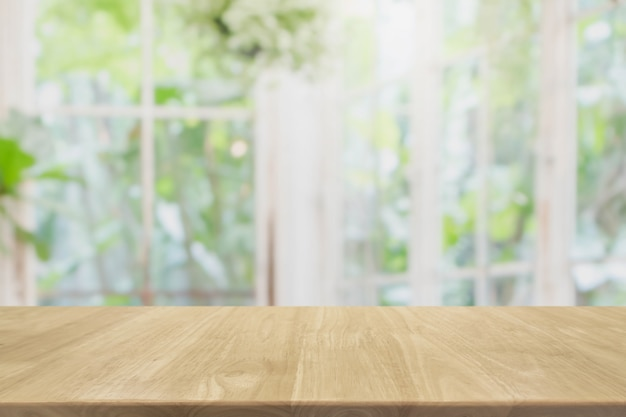 Empty wood table top and blurred of interior room with window view