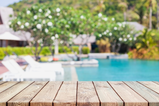 Empty wood table top and blurred swimming pool in tropical resort in summer banner background - can used for display or montage your products.