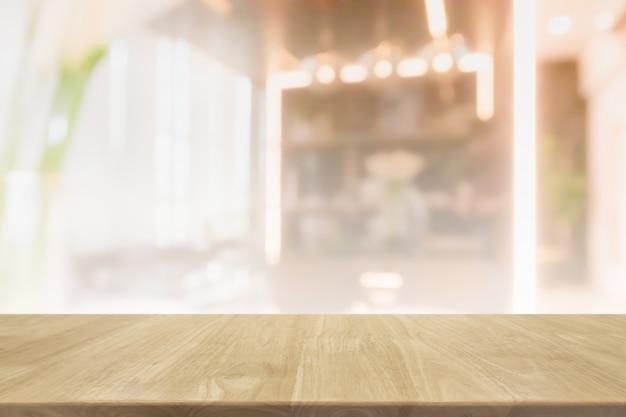 흐릿한 보케 카페 및 레스토랑 내부 배너 배경의 빈 나무 테이블 상단 - 제품을 표시하거나 몽타주하는 데 사용할 수 있습니다.