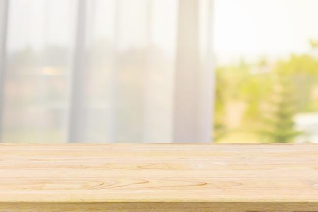 窓付きカーテンのぼかしに空の木製テーブルトップ
