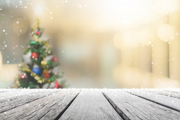 Bokeh와 흐림에 빈 나무 테이블 상단 크리스마스 트리와 눈으로 창 배너 배경에 새 해 장식-디스플레이에 사용하거나 제품을 몽타주 할 수 있습니다.