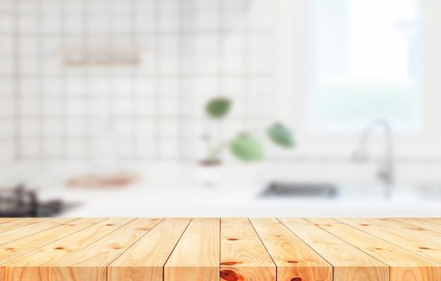Пустую деревянную столешницу на размытом фоне кухонной стойки можно использовать для демонстрации