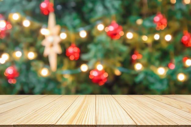 제품 디스플레이를 위한 장식 보케 밝은 배경이 있는 추상 흐림 크리스마스 트리가 있는 빈 나무 테이블 상단