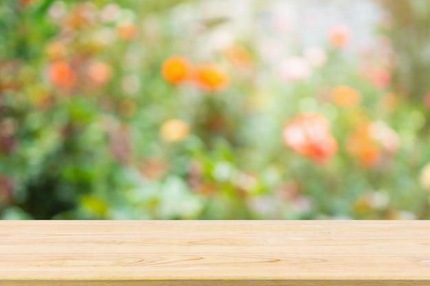 Пустая деревянная столешница с абстрактными размытыми красочными розовыми цветами в саду естественный свет боке для демонстрации продукта