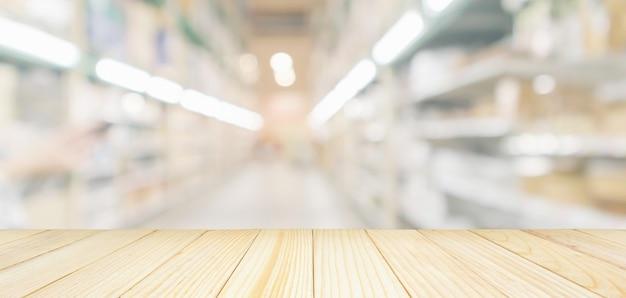 ぼやけたスーパーマーケットや倉庫の通路の背景を持つ空の木製テーブルトップ