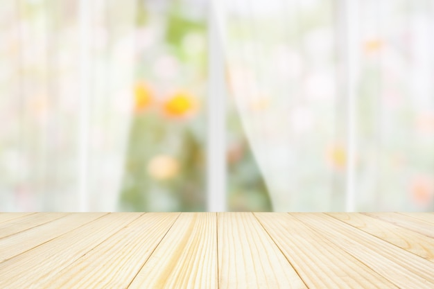 Empty wood table top with blur white curtain window and green garden background for product display template
