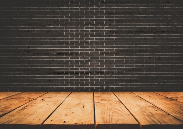 Empty wood table top with dark brick wall background.