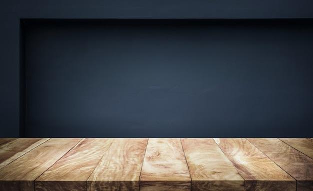 暗い壁の背景を持つ空の木製テーブルトップ。製品ディスプレイの作成または主要な視覚的レイアウトの設計用
