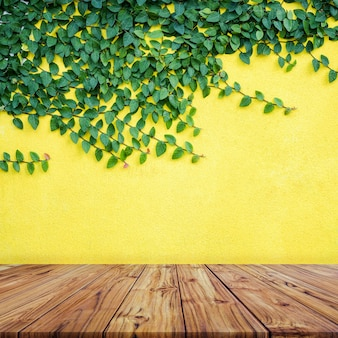 Empty wood table top with green leaves on yellow concrete wall backgroundign