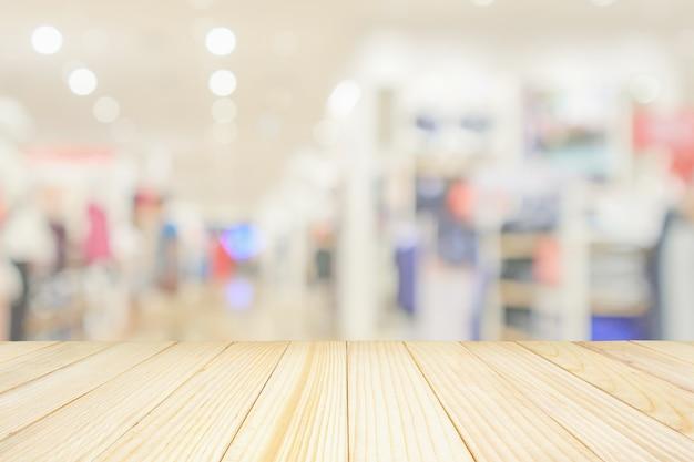 モダンな衣料品店のインテリアと空の木製テーブルトップは、製品のディスプレイ用のボケ光で抽象的な焦点ぼけの背景をぼかします
