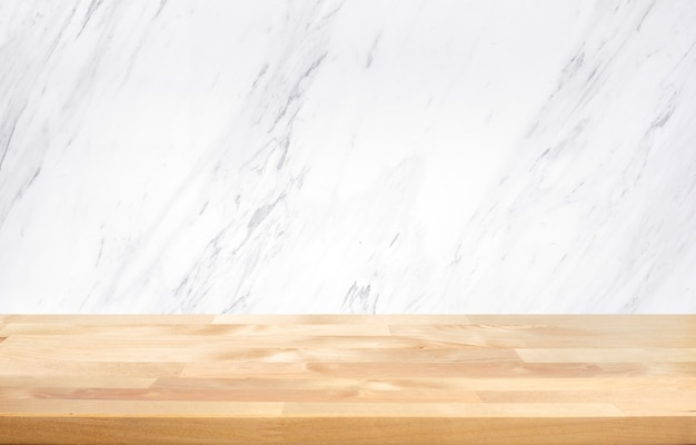 Empty wood table top with white marble wall background.