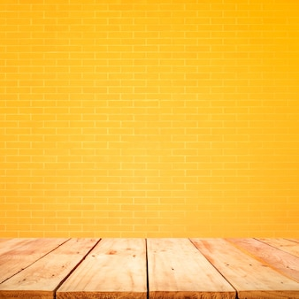 Empty wood table top with yellow brick wall background.for create product display or design key visual layout
