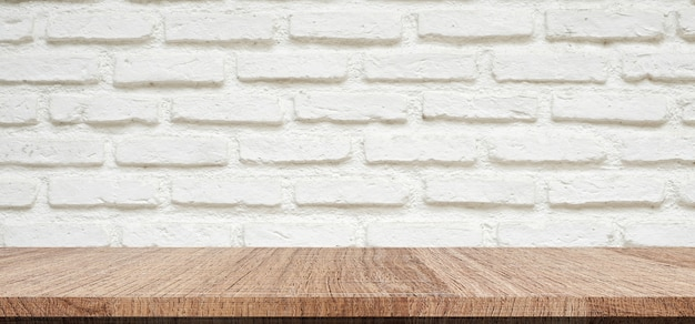 Empty wood table over white brick wall background
