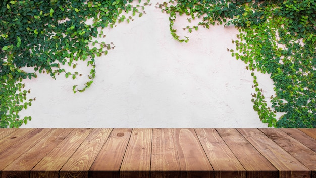Empty wood table with ivy leaves on cement wall background.