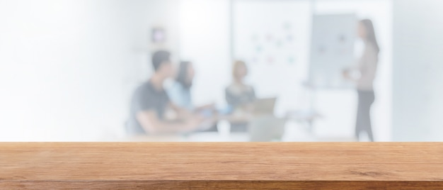Empty wood tabletop and blurred bokeh people working in office interior space banner background.