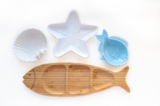 魚、ヒトデ、貝殻の形をした空の木とセラミックのプレート。