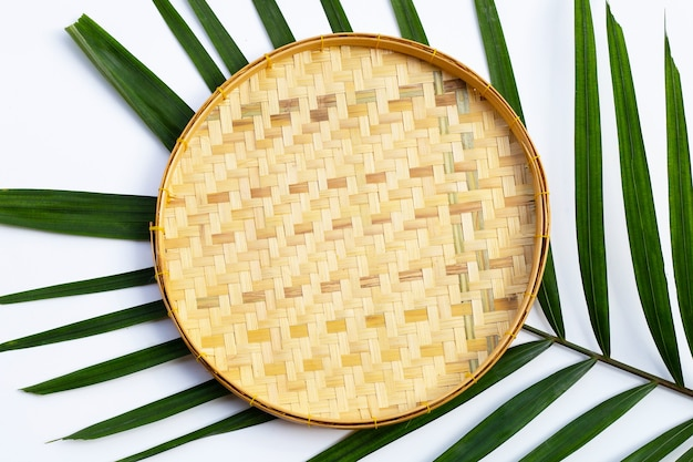 Empty wooden bamboo threshing basket on tropical palm leaves on white background.