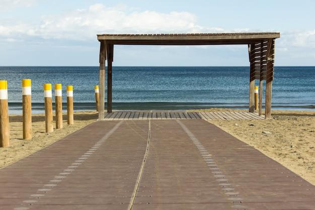 Empty wooden beach walk with blue ocean