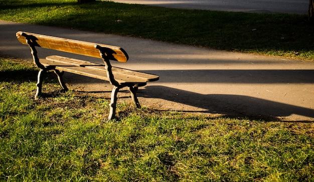 昼間の公園の空の木製ベンチ