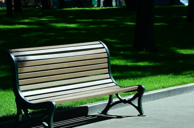 Empty wooden bench in the summer park against the green grass