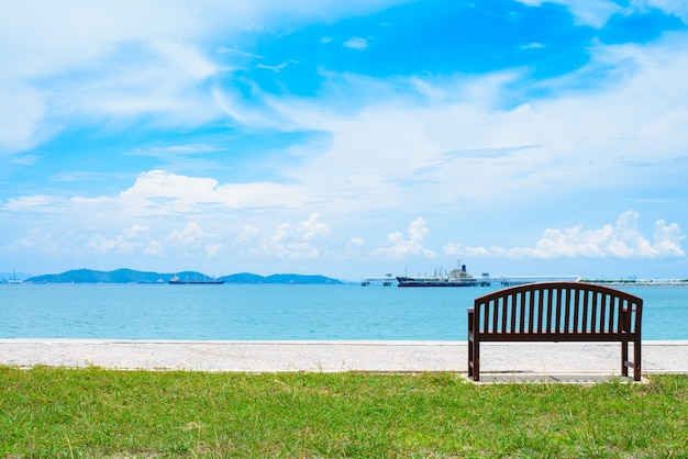 An empty wooden bench with a viewpoint looking out to sea.