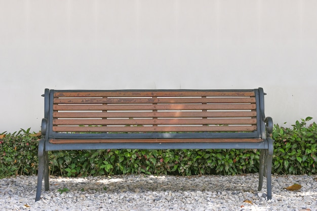 Empty wooden bench with white copy space wall as background.