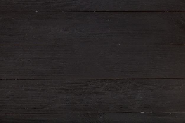 Empty wooden black table made of wood planks, simple texture background, clear dark grey desk blackboard, top view from above