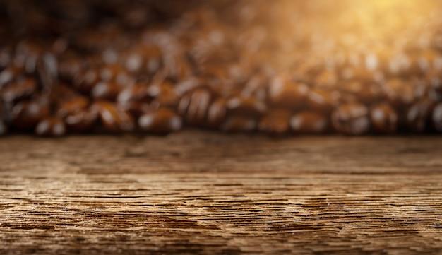 흐릿한 커피 콩 배경 앞의 빈 나무 판자. 공간을 복사합니다.