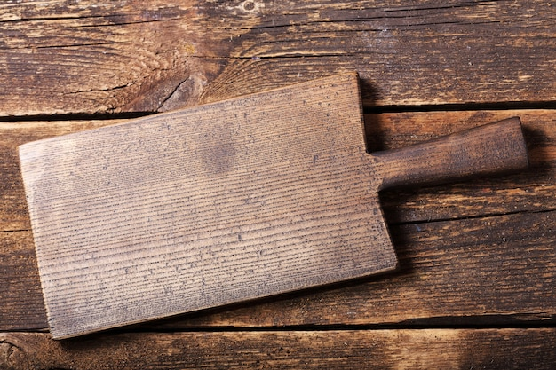 Пустая деревянная доска на старом деревянном столе, вид сверху