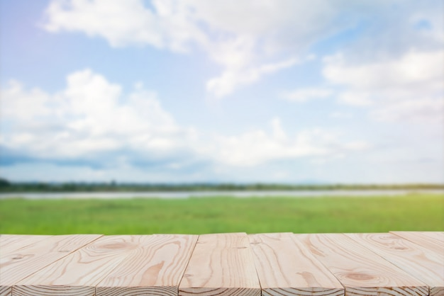 Empty wooden board table top on of blurred blue sky and river  background. copy space