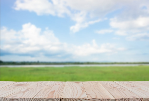 Empty wooden board table top on of blurred blue sky and river  background. with copyspace for display or montage your products