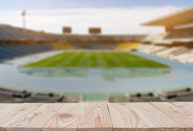 Empty wooden board table top on of blurred football (soccer) field background.