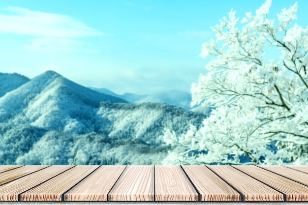 Empty wooden board top table in front of blurred snow mountain view