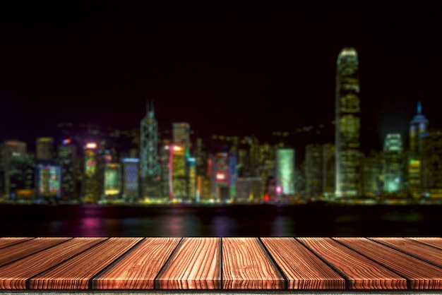 Empty wooden board top table in front of night city blurred background.